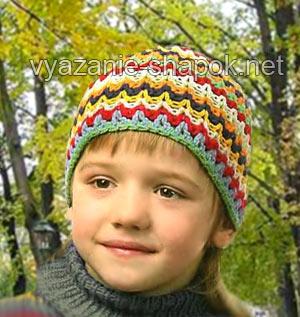 Эта симпатичная вязаная шапочка подойдет мальчику или девочке возраста 6-7 лет. Для нее нужны остатки пряжи нескольких цветов